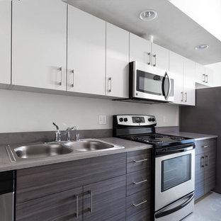 サクラメントのインダストリアルスタイルのおしゃれなキッチン (ダブルシンク、フラットパネル扉のキャビネット、中間色木目調キャビネット、クオーツストーンカウンター、シルバーの調理設備の、コンクリートの床) の写真