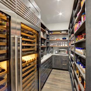 Imagen de cocina en L, moderna, grande, con despensa, armarios estilo shaker, puertas de armario de madera en tonos medios, encimera de cuarzo compacto, electrodomésticos de acero inoxidable, suelo de madera en tonos medios y una isla