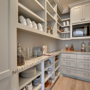 Large classic l-shaped kitchen pantry in Minneapolis with a belfast sink, recessed-panel cabinets, white cabinets, grey splashback, metro tiled splashback, stainless steel appliances, light hardwood flooring and an island.