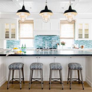 ロサンゼルスの広いビーチスタイルのおしゃれなキッチン (エプロンフロントシンク、落し込みパネル扉のキャビネット、白いキャビネット、ソープストーンカウンター、青いキッチンパネル、セラミックタイルのキッチンパネル、シルバーの調理設備、淡色無垢フローリング、ベージュの床、黒いキッチンカウンター、格子天井) の写真