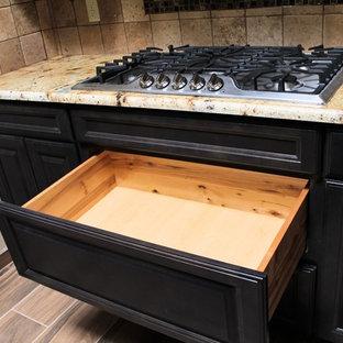 オースティンの中サイズのサンタフェスタイルのおしゃれなキッチン (アンダーカウンターシンク、レイズドパネル扉のキャビネット、グレーのキャビネット、御影石カウンター、ベージュキッチンパネル、セラミックタイルのキッチンパネル、シルバーの調理設備の、セラミックタイルの床) の写真