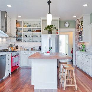 Geschlossene, Mittelgroße Landhausstil Küche in U-Form mit Landhausspüle, Schrankfronten im Shaker-Stil, weißen Schränken, Arbeitsplatte aus Holz, Küchenrückwand in Weiß, Rückwand aus Metrofliesen, Küchengeräten aus Edelstahl, Teppichboden, Kücheninsel, braunem Boden und brauner Arbeitsplatte in Seattle