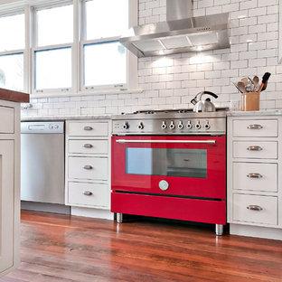 Exempel på ett avskilt, mellanstort lantligt brun brunt u-kök, med en rustik diskho, skåp i shakerstil, vita skåp, träbänkskiva, vitt stänkskydd, stänkskydd i tunnelbanekakel, rostfria vitvaror, heltäckningsmatta, en köksö och brunt golv