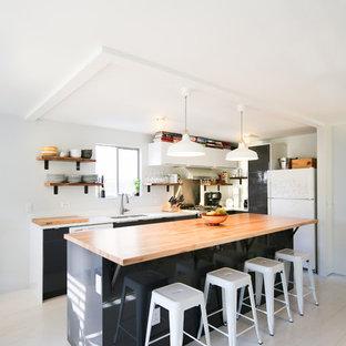 Esempio di una cucina minimalista di medie dimensioni con lavello a vasca singola, ante lisce, ante bianche, top in legno, paraspruzzi bianco, elettrodomestici in acciaio inossidabile, pavimento in compensato e isola