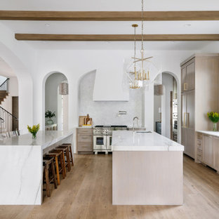 Huge mediterranean kitchen pictures - Inspiration for a huge mediterranean l-shaped light wood floor and beige floor kitchen remodel in Austin with an undermount sink, shaker cabinets, beige cabinets, white backsplash, paneled appliances, two islands and white countertops