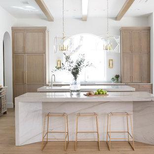 Imagen de cocina mediterránea con fregadero bajoencimera, armarios estilo shaker, puertas de armario de madera clara, electrodomésticos de acero inoxidable, suelo de madera clara, dos o más islas y encimeras blancas