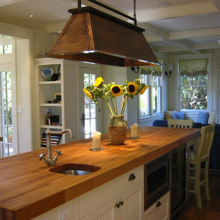 Example of a trendy kitchen design in San Francisco with an undermount sink, white cabinets and wood countertops