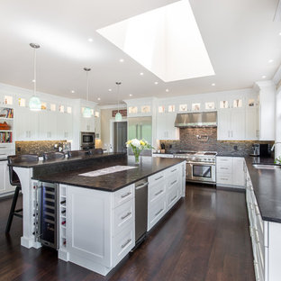 Design ideas for a large transitional u-shaped eat-in kitchen in Other with shaker cabinets, white cabinets, with island, a double-bowl sink, concrete benchtops, brown splashback, matchstick tile splashback, stainless steel appliances, dark hardwood floors, brown floor and grey benchtop.