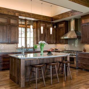 他の地域の広いラスティックスタイルのおしゃれなキッチン (アンダーカウンターシンク、シェーカースタイル扉のキャビネット、濃色木目調キャビネット、クオーツストーンカウンター、ガラスタイルのキッチンパネル、シルバーの調理設備、ベージュキッチンパネル、濃色無垢フローリング) の写真