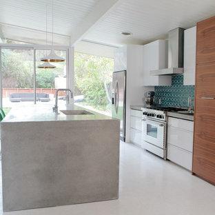 サンフランシスコのモダンスタイルのおしゃれなアイランドキッチン (アンダーカウンターシンク、フラットパネル扉のキャビネット、中間色木目調キャビネット、コンクリートカウンター、青いキッチンパネル、セラミックタイルのキッチンパネル、シルバーの調理設備の、クッションフロア) の写真