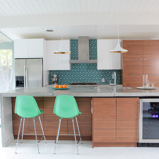 This is an example of a midcentury galley eat-in kitchen in San Francisco with an undermount sink, flat-panel cabinets, medium wood cabinets, concrete benchtops, blue splashback, ceramic splashback, stainless steel appliances, vinyl floors and with island.