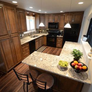 Idéer för mellanstora vintage kök, med en undermonterad diskho, luckor med upphöjd panel, skåp i mellenmörkt trä, bänkskiva i kvarts, grått stänkskydd, stänkskydd i glaskakel, svarta vitvaror, mellanmörkt trägolv och en halv köksö