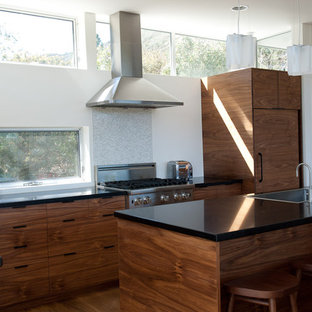 Inspiration for a contemporary l-shaped kitchen in Los Angeles with panelled appliances, an undermount sink, shaker cabinets, dark wood cabinets and solid surface benchtops.