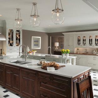 Cette image montre une grand cuisine américaine traditionnelle en U avec un évier 2 bacs, des portes de placard blanches, un plan de travail en verre, une crédence grise, une crédence en carrelage métro, un électroménager en acier inoxydable, un sol en carrelage de céramique et 2 îlots.