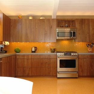 他の地域の広いモダンスタイルのおしゃれなキッチン (フラットパネル扉のキャビネット、中間色木目調キャビネット、オレンジのキッチンパネル、サブウェイタイルのキッチンパネル、シルバーの調理設備、アイランドなし、リノリウムの床、アンダーカウンターシンク、クオーツストーンカウンター) の写真