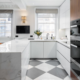This is an example of a mid-sized contemporary u-shaped open plan kitchen in Surrey with a double-bowl sink, flat-panel cabinets, white cabinets, marble benchtops, white splashback, marble splashback, black appliances, marble floors, a peninsula, multi-coloured floor and white benchtop.