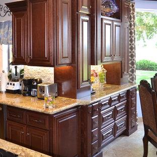 フェニックスの中くらいのトラディショナルスタイルのおしゃれなキッチン (レイズドパネル扉のキャビネット、中間色木目調キャビネット、御影石カウンター、シルバーの調理設備、ライムストーンの床) の写真