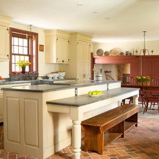 フィラデルフィアの中くらいのカントリー風おしゃれなキッチン (レイズドパネル扉のキャビネット、ベージュのキャビネット、レンガの床、エプロンフロントシンク、パネルと同色の調理設備、赤い床、コンクリートカウンター、グレーのキッチンカウンター) の写真