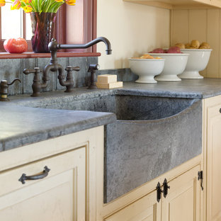 This is an example of a mid-sized country single-wall eat-in kitchen in Philadelphia with a farmhouse sink, raised-panel cabinets, beige cabinets, concrete benchtops, panelled appliances, brick floors, with island, red floor and grey benchtop.