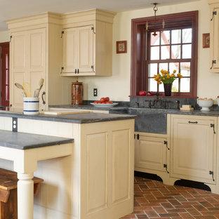 フィラデルフィアの中くらいのカントリー風おしゃれなキッチン (エプロンフロントシンク、レイズドパネル扉のキャビネット、レンガの床、パネルと同色の調理設備、ベージュのキャビネット、コンクリートカウンター、赤い床、グレーのキッチンカウンター) の写真
