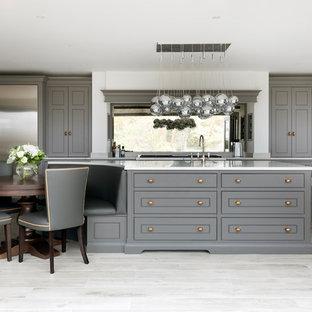 Klassisk inredning av ett mellanstort l-kök, med grå skåp, rostfria vitvaror, en köksö, beiget golv och fönster som stänkskydd