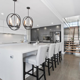 Photo of a mid-sized contemporary galley kitchen in Perth with an undermount sink, flat-panel cabinets, white splashback, stainless steel appliances, grey floor and multiple islands.