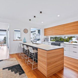 Design ideas for a large beach style galley open plan kitchen in Central Coast with an undermount sink, flat-panel cabinets, medium wood cabinets, mirror splashback, stainless steel appliances, a peninsula, brown floor and white benchtop.