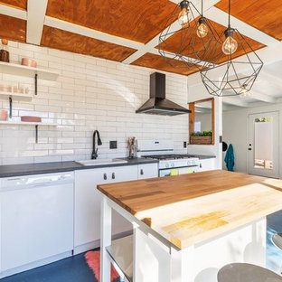 Small contemporary l-shaped open plan kitchen in Los Angeles with a drop-in sink, flat-panel cabinets, white cabinets, white splashback, white appliances, concrete floors, with island, blue floor, grey benchtop, zinc benchtops and subway tile splashback.