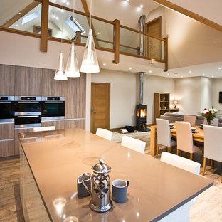 Modelo de cocina comedor actual con armarios con paneles lisos, puertas de armario de madera oscura, electrodomésticos con paneles, suelo de madera en tonos medios y una isla