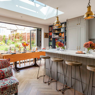 Medium sized bohemian single-wall kitchen in London with shaker cabinets, grey cabinets, marble worktops, white splashback, an island and beige floors.