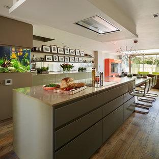 Diseño de cocina contemporánea, abierta, con armarios con paneles lisos, encimera de acrílico, salpicadero con efecto espejo, suelo de madera en tonos medios y una isla