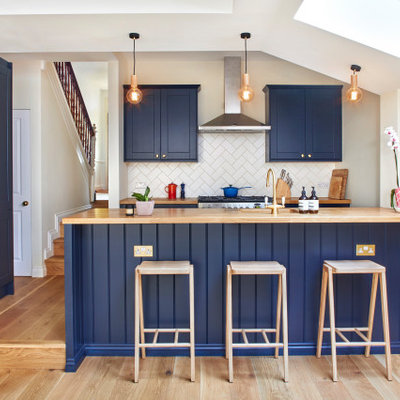 Inspiration for a transitional u-shaped medium tone wood floor and brown floor kitchen remodel in London with an undermount sink, shaker cabinets, blue cabinets, wood countertops, white backsplash, paneled appliances, a peninsula and brown countertops