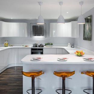 Medium sized modern u-shaped kitchen/diner in West Midlands with a built-in sink, white cabinets, white splashback, stainless steel appliances, dark hardwood flooring, a breakfast bar, brown floors, white worktops and flat-panel cabinets.