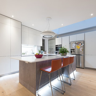Photo of a medium sized modern l-shaped kitchen in Hertfordshire with flat-panel cabinets, white cabinets, stainless steel appliances, light hardwood flooring, an island and beige floors.