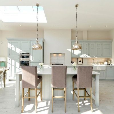 Eat-in kitchen - transitional galley eat-in kitchen idea in London with a farmhouse sink, shaker cabinets, blue cabinets, stainless steel appliances and an island