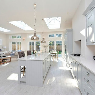 This is an example of a traditional open plan kitchen in London with shaker cabinets, grey cabinets and an island.