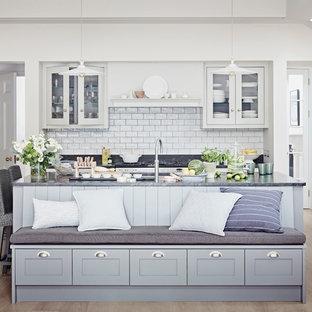 Imagen de cocina contemporánea con fregadero bajoencimera, armarios tipo vitrina, puertas de armario blancas, salpicadero blanco, salpicadero de azulejos tipo metro, suelo de madera clara, una isla, suelo beige y encimera de granito