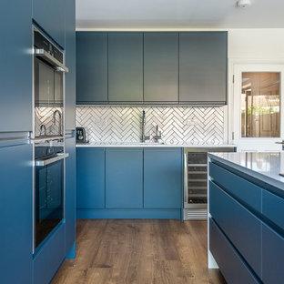 ロンドンの広いモダンスタイルのおしゃれなキッチン (ドロップインシンク、フラットパネル扉のキャビネット、青いキャビネット、珪岩カウンター、白いキッチンパネル、サブウェイタイルのキッチンパネル、シルバーの調理設備、クッションフロア、白いキッチンカウンター) の写真
