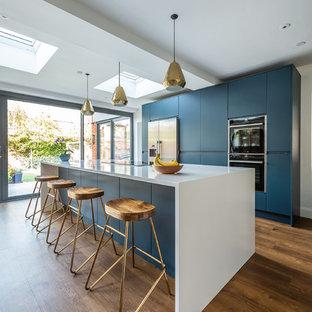 Cette image montre une grande cuisine ouverte parallèle design avec un placard à porte plane, des portes de placard bleues, un plan de travail en quartz, un électroménager en acier inoxydable, un sol en vinyl, un îlot central, un plan de travail blanc et un sol marron.