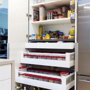 メルボルンの広いモダンスタイルのおしゃれなキッチン (アンダーカウンターシンク、フラットパネル扉のキャビネット、白いキャビネット、クオーツストーンカウンター、グレーのキッチンパネル、ガラス板のキッチンパネル、シルバーの調理設備、セラミックタイルの床、オレンジの床) の写真