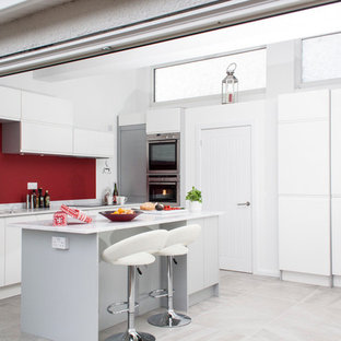 Small industrial eat-in kitchen photos - Example of a small urban l-shaped ceramic floor eat-in kitchen design in Cardiff with flat-panel cabinets, white cabinets, an island, a drop-in sink, solid surface countertops, red backsplash and stainless steel appliances
