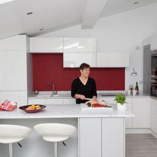 Idee per una piccola cucina design con lavello da incasso, ante lisce, ante bianche, top in superficie solida, paraspruzzi rosso, elettrodomestici in acciaio inossidabile, pavimento con piastrelle in ceramica e isola