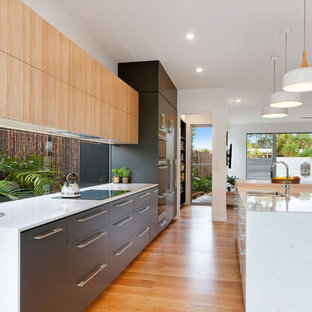 Inspiration for a large beach style galley open plan kitchen in Sunshine Coast with flat-panel cabinets, medium hardwood floors, multiple islands, brown floor, white benchtop, an undermount sink, window splashback and panelled appliances.