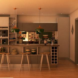 Zweizeilige, Mittelgroße Moderne Wohnküche mit integriertem Waschbecken, flächenbündigen Schrankfronten, grauen Schränken, Quarzit-Arbeitsplatte, Küchenrückwand in Metallic, Rückwand aus Spiegelfliesen, Küchengeräten aus Edelstahl, hellem Holzboden, Kücheninsel, braunem Boden und grauer Arbeitsplatte in London
