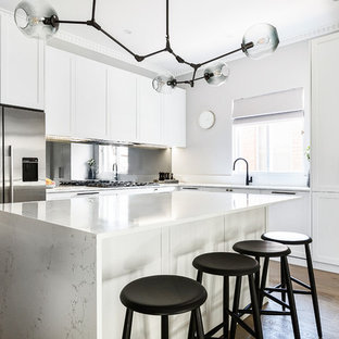 Design ideas for a large transitional l-shaped open plan kitchen in Sydney with an undermount sink, shaker cabinets, white cabinets, quartz benchtops, mirror splashback, medium hardwood floors, with island, brown floor, white benchtop and stainless steel appliances.