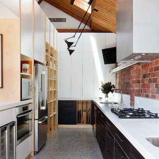 Inspiration for an industrial single-wall kitchen in Melbourne with flat-panel cabinets, black cabinets, stainless steel appliances and no island.