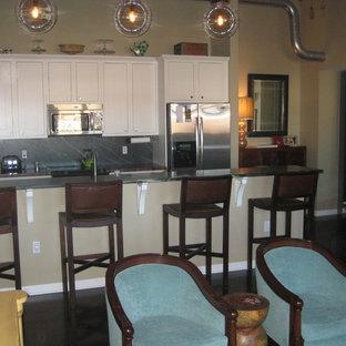 他の地域のインダストリアルスタイルのおしゃれなペニンシュラキッチン (エプロンフロントシンク、シェーカースタイル扉のキャビネット、白いキャビネット、ソープストーンカウンター、黒いキッチンパネル、石スラブのキッチンパネル、シルバーの調理設備の、濃色無垢フローリング) の写真