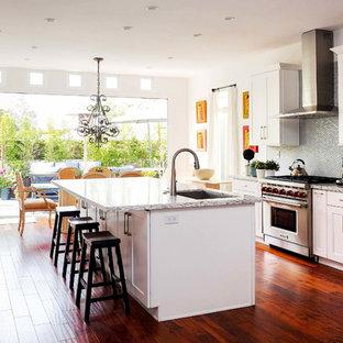 ロサンゼルスの巨大なエクレクティックスタイルのおしゃれなキッチン (ドロップインシンク、シェーカースタイル扉のキャビネット、白いキャビネット、クオーツストーンカウンター、グレーのキッチンパネル、ガラスタイルのキッチンパネル、シルバーの調理設備、無垢フローリング、茶色い床、マルチカラーのキッチンカウンター) の写真