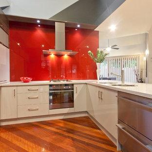 Kleine Moderne Wohnküche in U-Form mit Doppelwaschbecken, Quarzwerkstein-Arbeitsplatte, Küchenrückwand in Rot, Glasrückwand und Küchengeräten aus Edelstahl in Melbourne