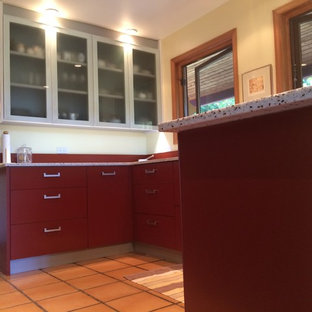 Large contemporary u-shaped kitchen in Vancouver with an undermount sink, flat-panel cabinets, red cabinets, recycled glass benchtops, red splashback and terra-cotta floors.